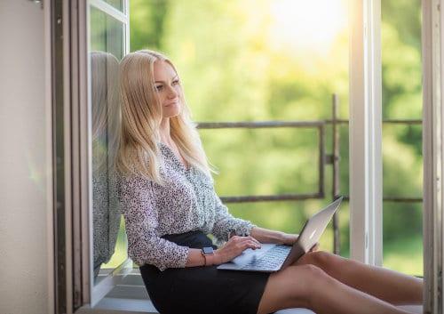Kobieta siedzi przy oknie z laptopem na kolanach