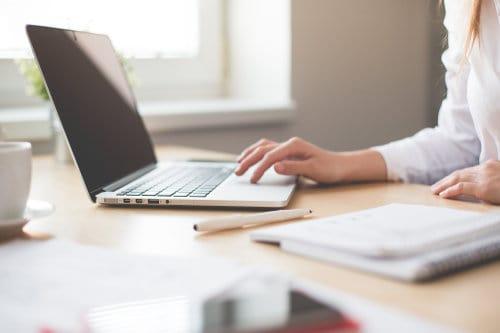 Kobieta pracuje przy laptopie w firmie