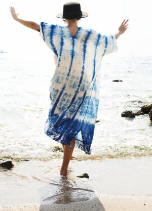 Kobieta w kapeluszu skacze po kamieniach na plaży