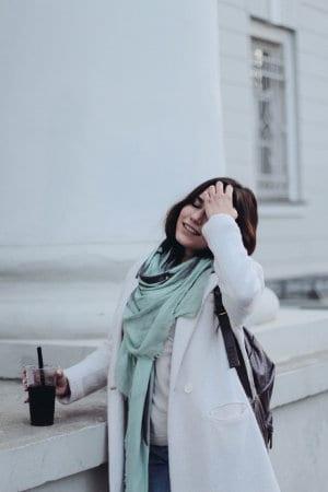 Kobieta w białym płaszczu trzyma w kubku napój ze słomką