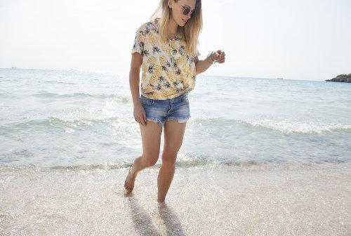 Kobieta w krótkich spodenkach chodzi brzegiem morza
