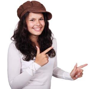 Kobieta w czapce wskazuje palcami
