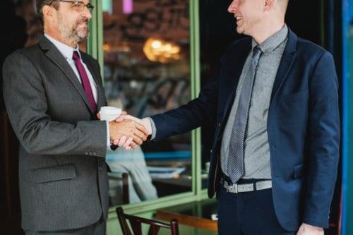 Dwóch mężczyzn podaje sobie dłonie w kawiarni