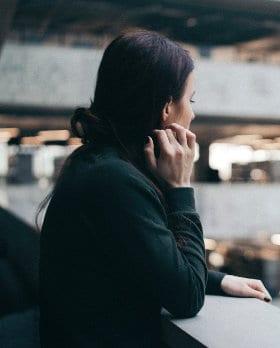 Kobieta opiera się o barierkę w galerii handlowej