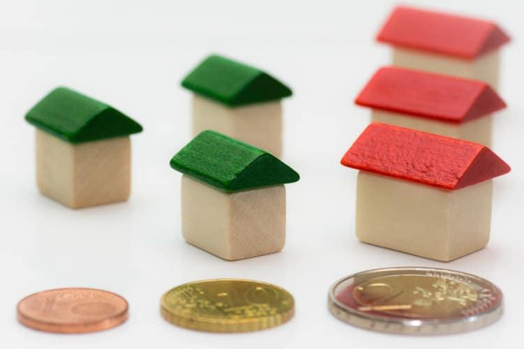 Małe drewniane domki i monety euro