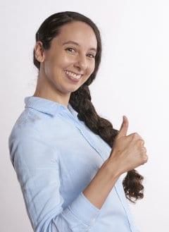 Kobieta pokazuje wyciągnięty ku górze kciuk