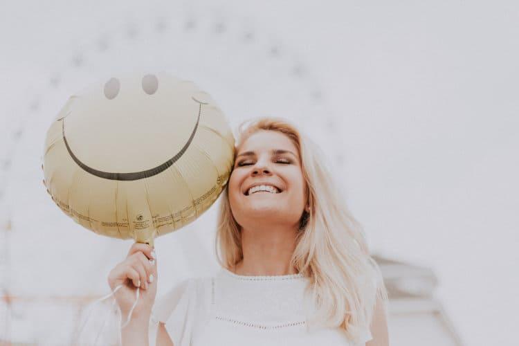 Uśmiechnięta kobieta trzyma w dłoni balon