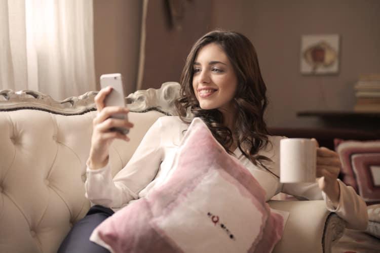 Kobieta leży na kanapie i sprawdza telefon komórkowy