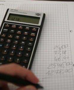Mężczyzna przelicza coś na kalkulatorze