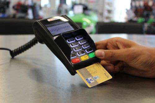 Mężczyzna płaci w sklepie kartą płatniczą