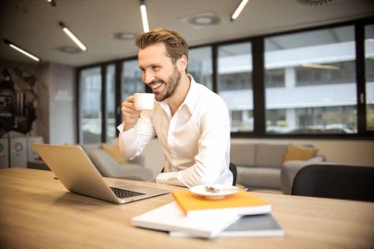 Uśmiechnięty mężczyzna pracuje przy laptopie i popija kawę