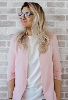 Kobieta w okularach i różowej marynarce
